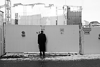 An elderly man takes a peek at new construction taking shape on the other side  of a gate in Hamburg Germany.