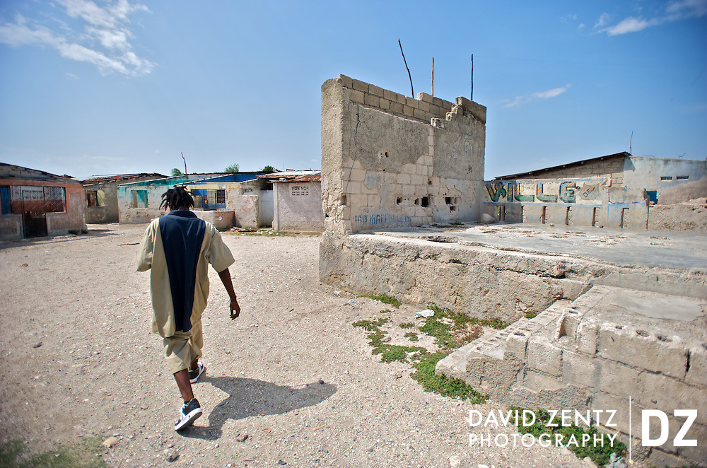 2Double, 21, walks through the barren Cite Soleil, where he has lived all his life, on July 19, 2008. By focusing on his musical interests he has been able to steer clear of the gang activity that is endemic to the poverty-stricken area.