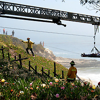 Santa Cruz firefighters hoist an injured man up to West Cliff Drive after he was reported lying motionless on the rocks 18-20 feet below the roadway at Fair Avenue in Santa Cruz, California on Sunday May 12, 2013. The man was breathing but unconscious and was airlifted to Stanford Hospital. <br />Photo by Shmuel Thaler/Santa Cruz Sentinel
