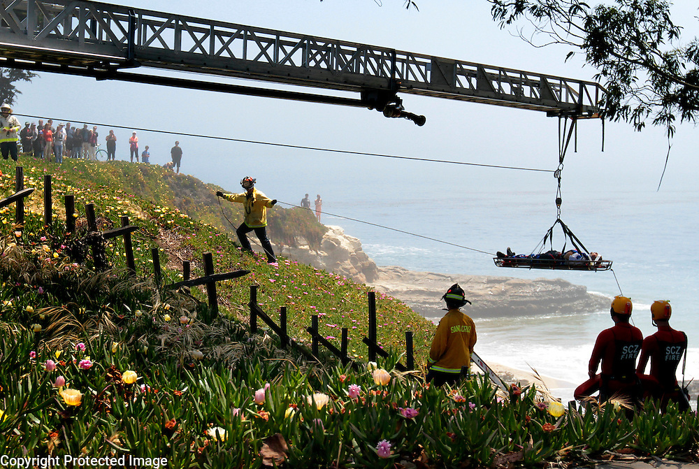 Santa Cruz firefighters hoist an injured man up to West Cliff Drive after he was reported lying motionless on the rocks 18-20 feet below the roadway at Fair Avenue in Santa Cruz, California on Sunday May 12, 2013. The man was breathing but unconscious and was airlifted to Stanford Hospital. <br />