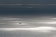 Fishing boat on sun dappled seas off the Purbeck coast, Dorset, UK.