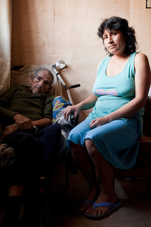 A woman sits with her father, who has tuberculosis, in their home on Monday, Apr. 6, 2009 in Ventanilla, Peru.