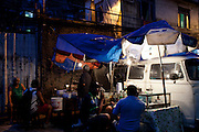 Customers share a dinner at an improvised snack bar in Rocinha slum in Rio de Janeiro, Brazil, Thursday, Feb. 28, 2013. Although Rocinha is technically classified as a neighborhood, many still refer to it as a favela. It developed from a shanty town into an urbanized slum. In November 2011, a security operation was executed where hundreds of police and military patrolled the streets of Rocinha to crackdown on rampant drug dealers and bring government control to the neighborhood.