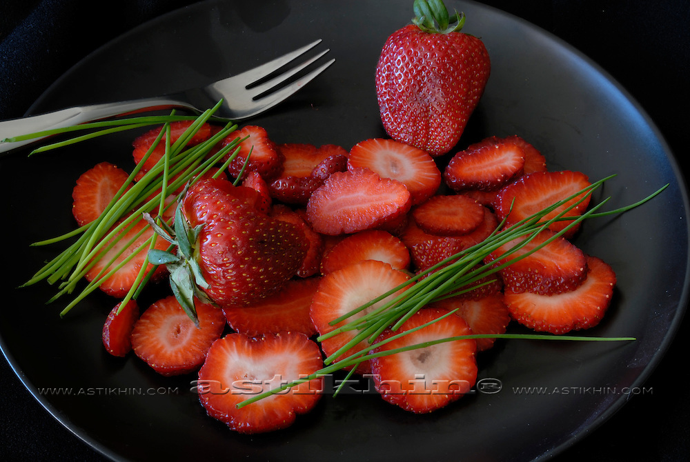 Chive and strawberry on plate.