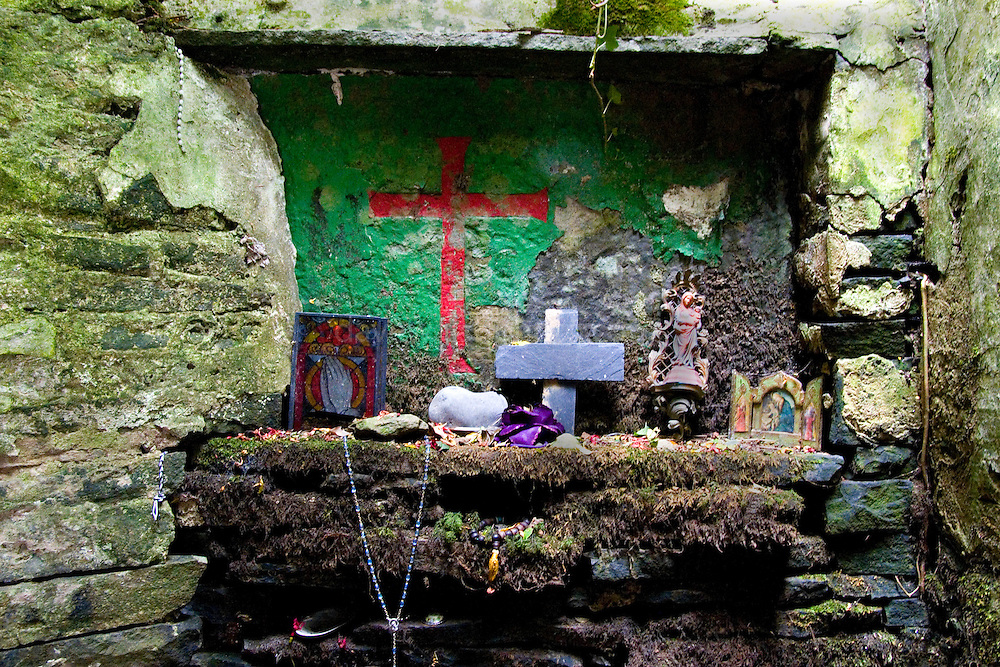 "On the Liscannor -  Doolin road, near the Cliffs of Moher, this ostensibly holy well is full of wonderful, decaying votive offerings. St. Brigid never actually existed in Christian times - in mythology she was the ""exalted one"" - daughter of the Dagda and therefore one of the Tuatha De Danann.....The ""cave"" at St. Brigit's Well is full of strange objects. Decaying statues, rotting dolls, faded masscards, abandoned prosthetic limbs, rosary beads, toys, polaroid photographs. All left as mementos, blessings, prayers for the dead, the ill and the future."