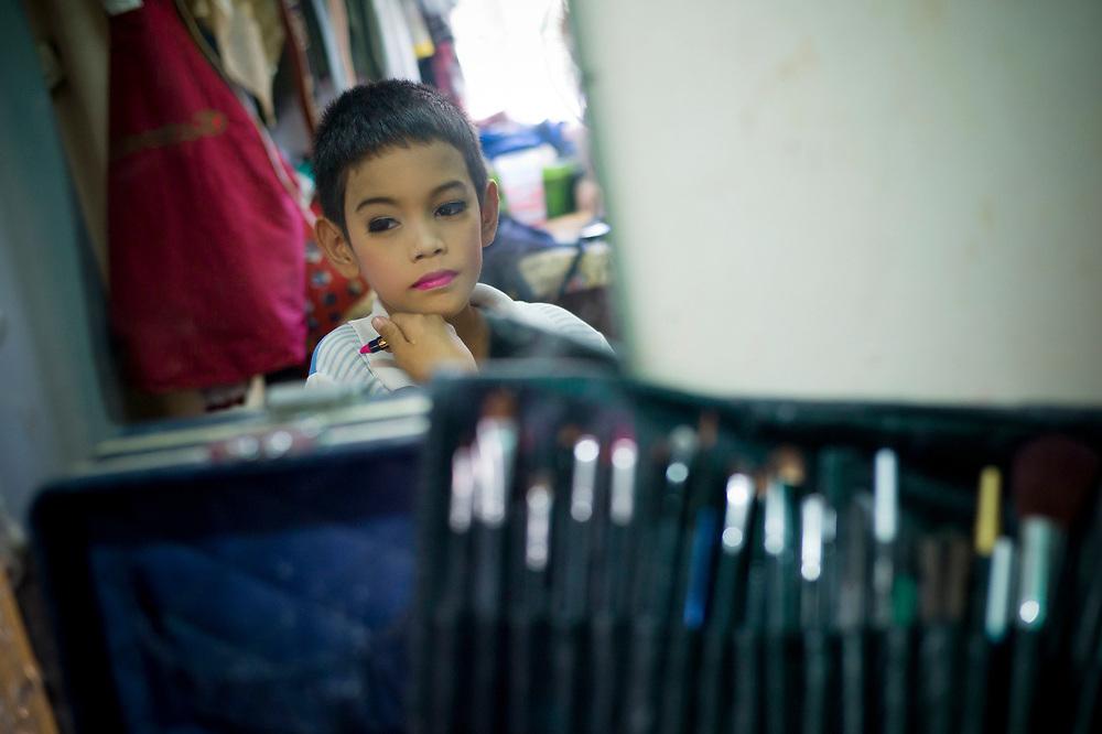 """Bangkok November 13, 2013<br /> Kafille is 6 years old looks through the mirror after his makeup. His mother had noticed since he was 3 years old, he already behaved as a little girl, showing signs of being feminine. His older brother, Aekachai, 23, is a ladyboy, and Kafille was definitely influenced by him.As her mother said: """"we can't do anything, he has to follow his heart and has to live his life the way he wants to""""Bangkok 13 novembre 2013<br /> Kafille a 6 ans et se regarde dans le miroir après son maquillage. Sa mère l'avait remarqué dès l'âge de 3 ans, il se comportait déjà comme une petite fille, montrant des signes de féminité. Son frère aîné, Aekachai, 23 ans, est une coccinelle, et Kafille a été définitivement influencé par lui, comme l'a dit sa mère : """"On ne peut rien faire, il doit suivre son coeur et vivre sa vie comme il le veut""""<br /> <br /> Traduit avec www.DeepL.com/Translator"""
