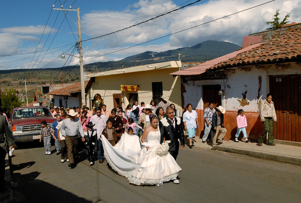 Following their wedding ceremony, the bride and groom walk to their reception through the streets of Lagunillas, Mexico accompanied by guests and well-wishers. Many couples like Liliana Hernandez, 24, and Sergio Salinas, 27, chose to marry in December when their town comes alive with the arrival of the norteños. Salinas works in home construction in town and his wife plans to become an ama de casa or housewife.