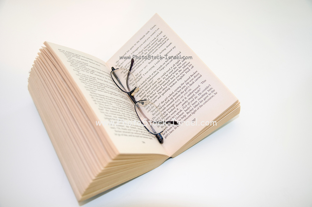 Open paperback book and reading glasses