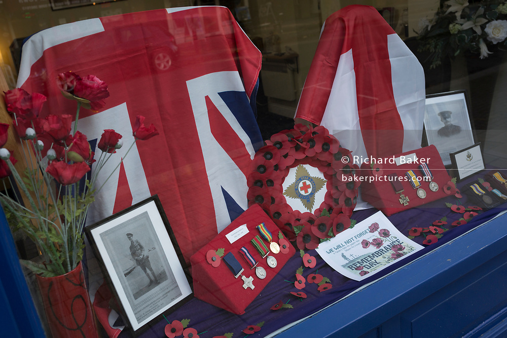 A window display of a high street funeral directors showing patriotic Union Jacks and replica medals of a local man, Second Lieutenant Reginald Cuthbert Chilvers of the Norfolk Regiment, a casualty in 1917 during WW1, on 7th November 2019, in Surbiton, London, England