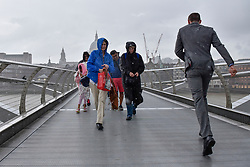 © Licensed to London News Pictures. 11/07/2017. London, UK. Tourists and office workers are caught in a downpour crossing the Millennium Bridge as rain arrives in the capital after several days of hot and dry weather. Photo credit : Stephen Chung/LNP