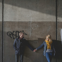 Two young adults holding hands against a harsh concrete background
