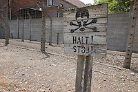 Sign with skull and crossed bones and the words Halt (german) and Stoj (polish) in front of electrified fences. Auschwitz 1 ,Poland.