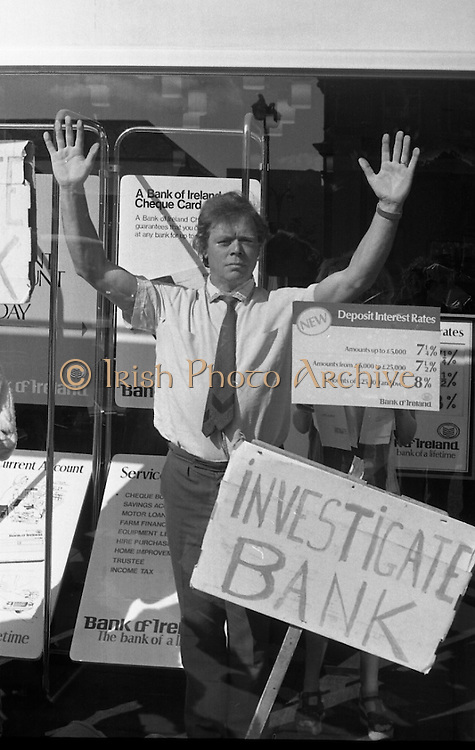 Fergus Rowan sits in at Bank of Ireland.  (J70)..1975..22.08.1975..08.22.1975..22nd August 1975..As a result of the 1970 bank strike which lasted for six months, the Rowan family business found itself in financial difficulties. During the strike the Rowans had had to accept cheques in good faith in order to stay in business. When the cheques came for settlement the bank refused as they stated that some were 'dodgy'. This put severe strain on the business which was eventually put into receivership.As part of the process the Rowan business beside the bank was put up for sale and was purchased by B.o I. Rowan was outraged and started a campaign against the bank which culminated in a sit in at the banks headquarters in Westmoreland St,Dublin. He also became a thorn in the side of the bank at the A.G.Ms raising many points...After receipt of the High Court Order, Mr Rowan is pictured defiantly standing in the bank window.