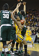 January 27 2010: Iowa guard Kachine Alexander (21) drives between defenders during the first half of an NCAA women's college basketball game at Carver-Hawkeye Arena in Iowa City, Iowa on January 27, 2010. Iowa defeated Michigan State 66-64.