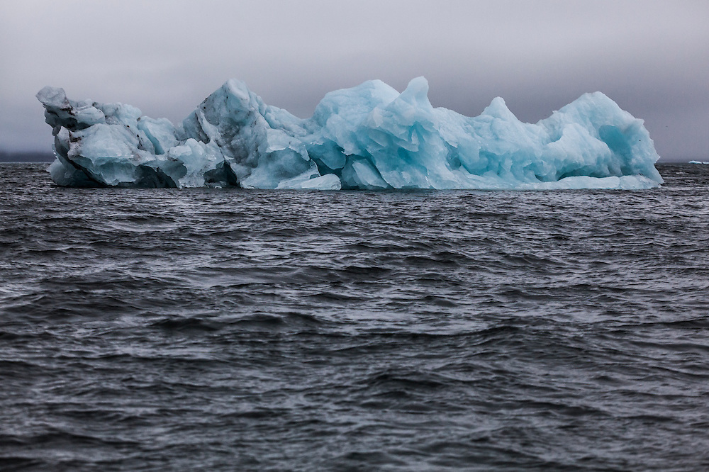 Portrait of a calved iceberg floating in choppy water in Hornsund, Svalbard.