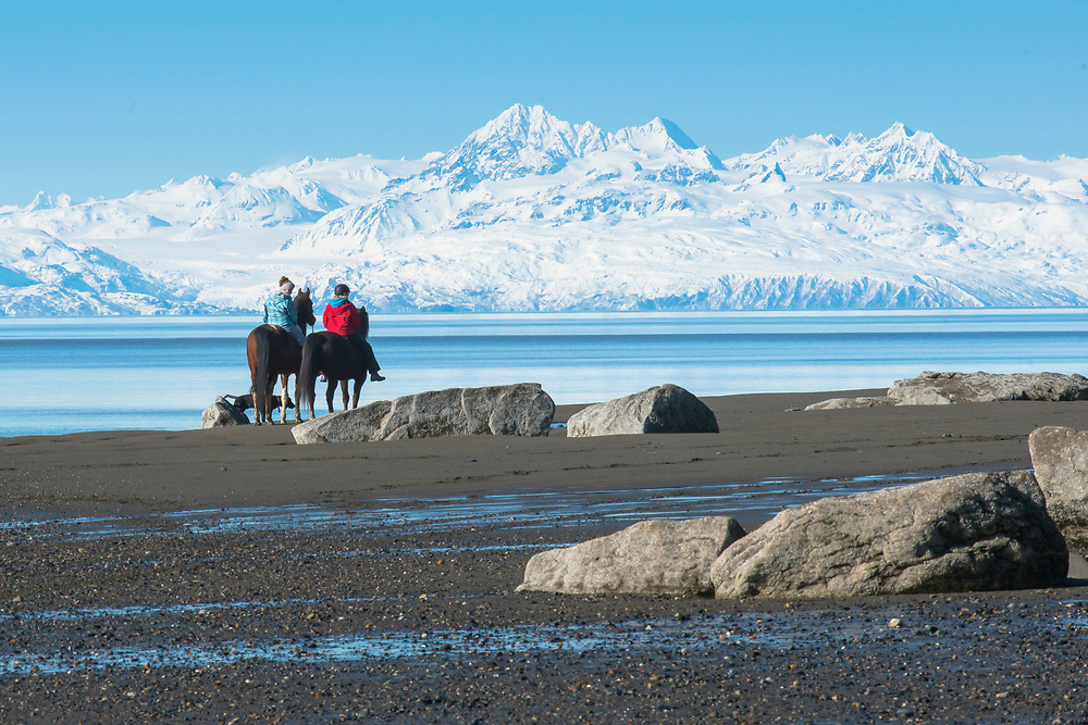Two women peacefully ride down the beach on horseback and admire the breathtaking view of Cook Inlet and the Alaska Range beyond.