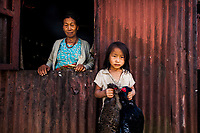 A grandmother and her granddaughter stand for a portrait outside of their home in an Angami village outside of Kohima, Nagaland, India. The young granddaughter is holding two colorful pheasants that will be cooked for lunch. The family grows Naga chilis on farmlands in their village.