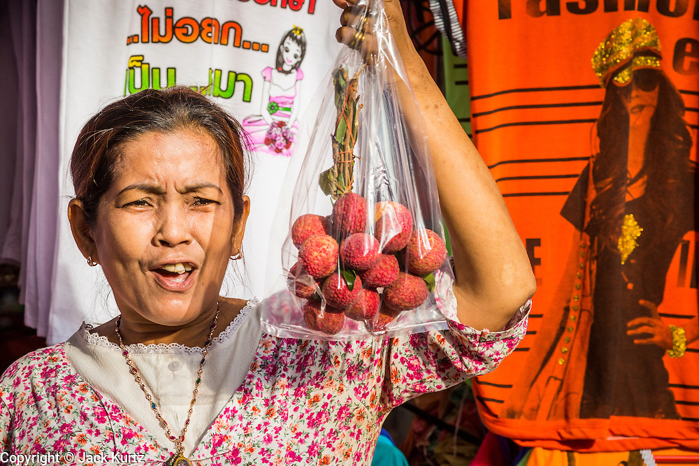 06 JUNE 2013 - BANGKOK, THAILAND:     A woman sells fruit on Krung Kasem Rd in front of Bobae Market in Bangkok. Bobae Market is a 30 year old market famous for fashion wholesale and is now very popular with exporters from around the world. Bobae Tower is next to the market and  advertises itself as having 1,300 stalls under one roof and claims to be the largest garment wholesale center in Thailand.       PHOTO BY JACK KURTZ