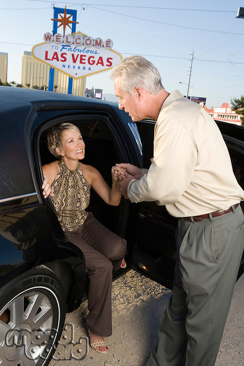Woman stepping out of limousine, man assisting