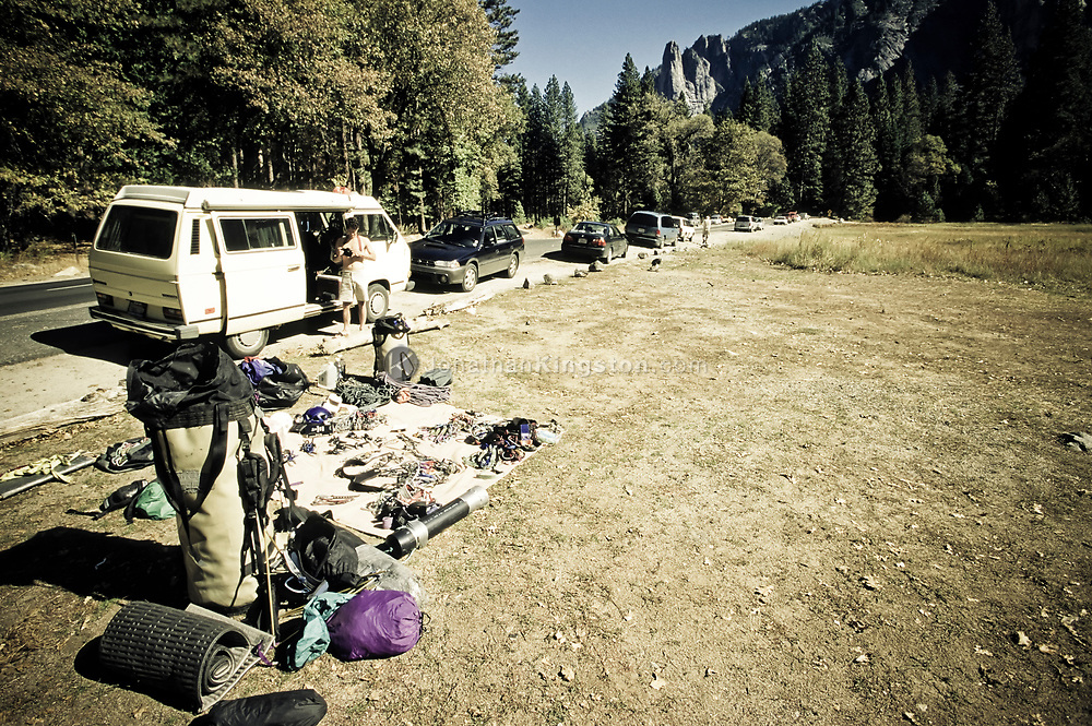 A man sorting rock climbing gear in front of a van in Yosemite National Park, California.  (releasecode: jk_mr1016) (Model Released)