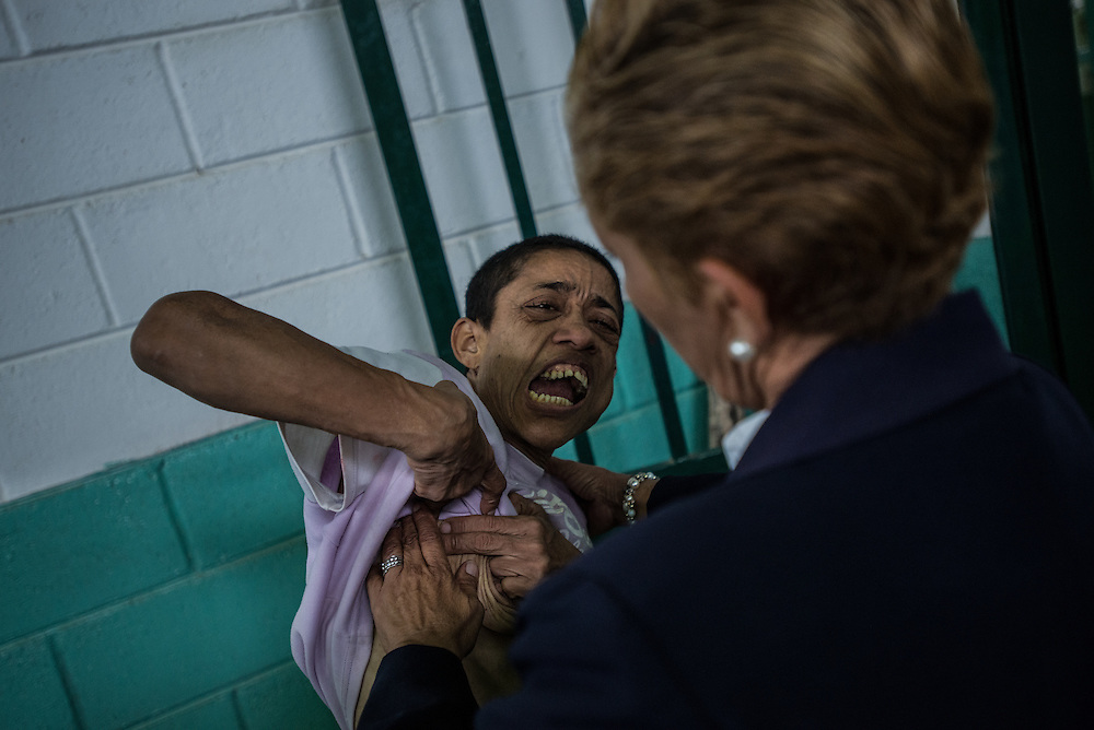 BARQUISIMETO, VENEZUELA - JULY 28, 2016: Schizophrenic patient, Levia Bracho cries to head nurse, Évila García, asking her to scratch her chest that is painfully itchy because she is infected with scabies. Bracho is violent, yells at other patients and gets into fights when she does not have all of her medications.  The economic crisis that has left Venezuela with little hard currency has also severely affected its public health system, crippling hospitals like El Pampero Psychiatric Hospital by leaving it without the resources it needs to take care of patients living there, the majority of whom have been abandoned by their families and rely completely on the state to meet their basic needs, and who could live much more fulfilling lives if they had the medicines that they need. The hospital does not even have basic hygiene or cleaning supplies.  There is no soap, no shampoo, no tooth paste, no toilet paper.  Patients relieve themselves in the common areas and patio area, and clean themselves only with water. Nearly every patient is infected with scabies because they do not have the resources to bathe properly or to have their threadbare, misfitted clothes washed as often as needed. To make matters worse, the hospital only has running water a few hours a day.  PHOTO: Meridith Kohut