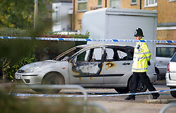 ©  London News Pictures. 15/10/2012. Harlow, UK. A policeman stood next to a burnt out car  on Barn Mead, Harlow, Essex where three children and a woman have died and three others are in hospital following a house fire. Two boys aged 13 and six, a girl aged 11 and the woman were declared dead at the scene. A nine-year-old boy and a three-year-old girl have serious burns and a man has minor burns. Photo credit : Ben Cawthra/LNP
