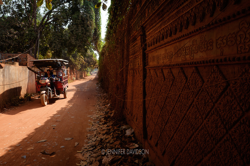 A tuk-tuk drives down a street in Siem Reap, Cambodia along the outside wall of a Buddist temple.
