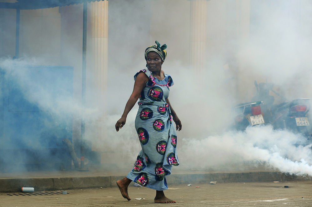 LOME, TOGO -  13-01-10   -  A woman runs as police shoot teargas at protesters. Shortly after gathering for the first in three days of planned demonstrations, protesters clashed with police in Lome, Togo on January 10. Opposition groups are calling for the resignation of President Faure Gnassingbe, whose family has been in power for over 40 years.   Photo by Daniel Hayduk