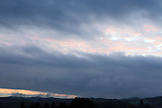 wind swept clouds with silhouetted panoramic landscape