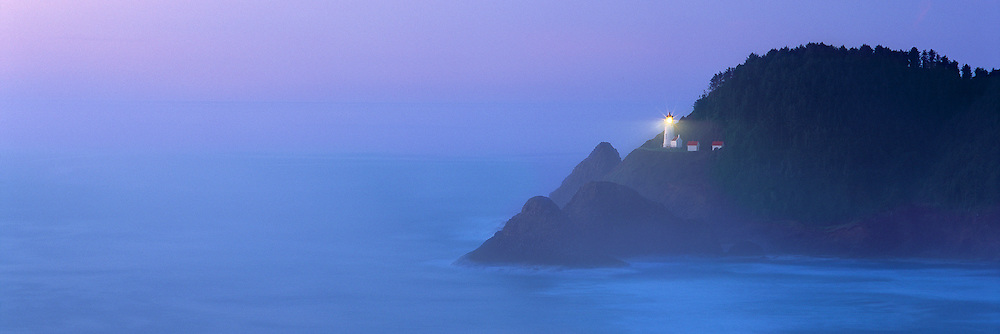 The beacon of Heceta Head Lighthouse shines through the periwinkle blue fog on the Oregon Coast.