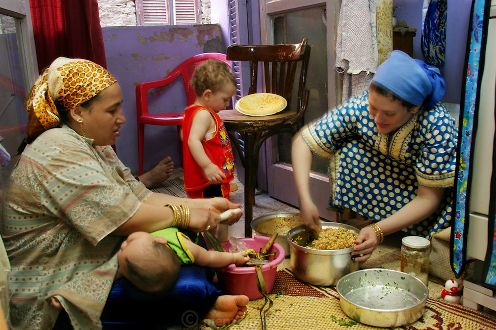 (MODEL RELEASED IMAGE).Nadia Ahmed (left) and her sister-in-law Abadeer make mahshi (stuffed food, in this case small eggplants) on the floor of Nadia's fourth-floor apartment. Heedless of the activity, baby Nancy sleeps on Nadia's lap; meanwhile, Abadeer's daughter Israa restlessly patrols the space. Hungry Planet: What the World Eats (p. 122).