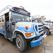 Chicken buses in the mud behind the Mercado Municipal (town market) in Antigua, Guatemala. From this extensive central bus interchange the routes radiate out across Guatemala. Often brightly painted, the chicken buses are retrofitted American school buses and provide a cheap mode of transport throughout the country.
