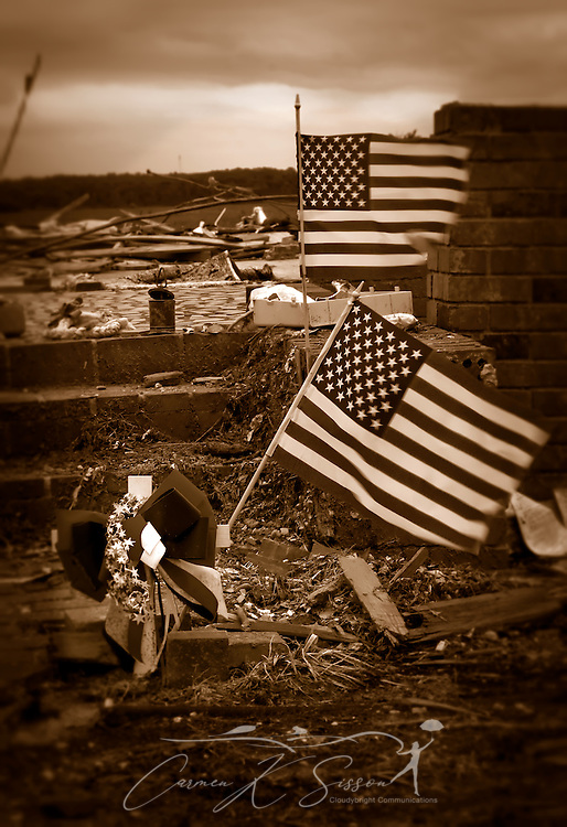 American flags wave amid the rubble of a demolished home May 15, 2011 in Smithville, Mississippi. Jesse Cox, 85, died in the house, and his wife, Nell Cox, 75, was seriously injured when an EF5 tornado swept through the town on April 27, 2011. (Photo by Carmen K. Sisson/Cloudybright)