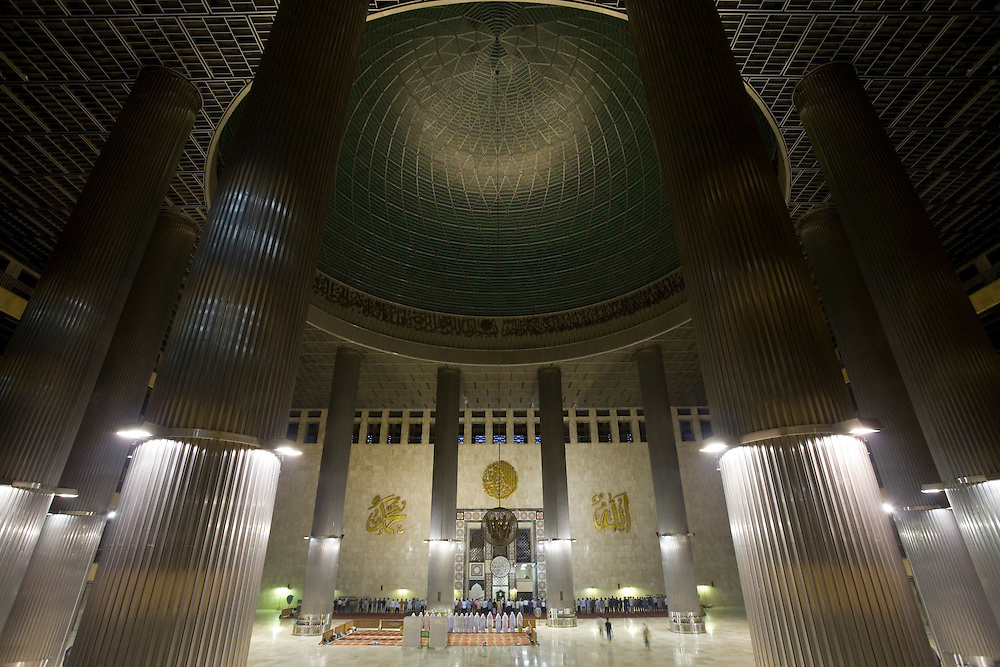 Indonesia, Jakarta, Interior view of worshippers arriving for evening prayers inside Mosque Mesjid Istiqlal at dusk