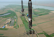 """HUAINAN, CHINA - JUNE 24: (CHINA OUT) <br /> <br /> Aerial Work For """"Anhui Power To Send The East"""" Project In Anhui<br /> <br /> Staff of Anhui Huainan power supply company examines wires on Huaishui River to eliminate equipment defects for the project of """"Anhui power to send the East"""" on June 24, 2014 in Huainan, Anhui province of China. <br /> ©Exclusivepix"""
