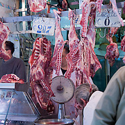 Butcher and meat market stall with fresh animal carcasses hanging from meat hooks, Capo Market, Palermo, Sicily, Italy