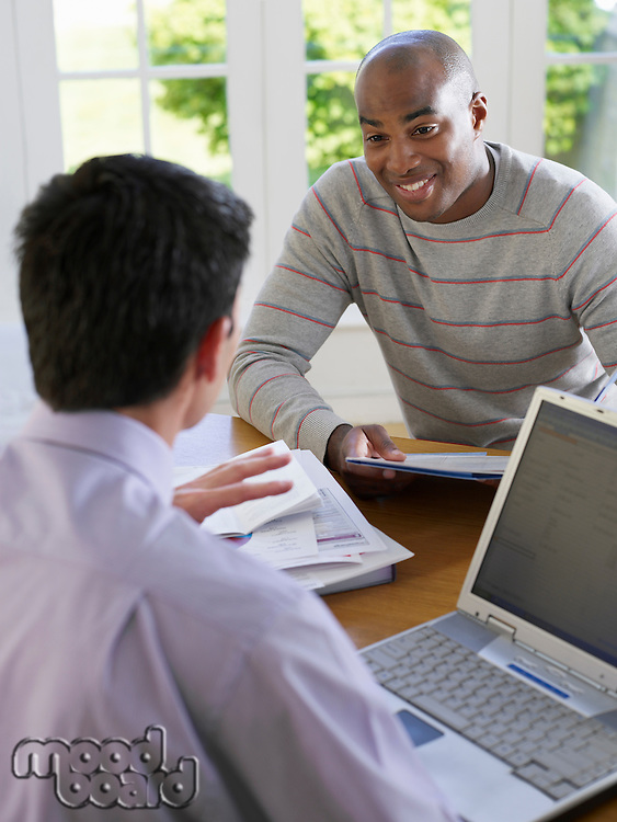 Man sitting at dinning table with financial advisor using laptop elevated view