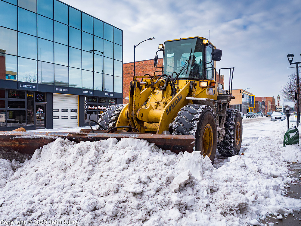 11 JANUARY 2020 - DES MOINES, IOWA:  A front end loader clears snow from a street in downtown Des Moines Saturday. The first significant snow in two months blanketed Des Moines Friday evening into Saturday morning. Meteorologists predicted up to six inches of snow overnight but by Saturday morning only about 3 inches had fallen in central Des Moines.     PHOTO BY JACK KURTZ