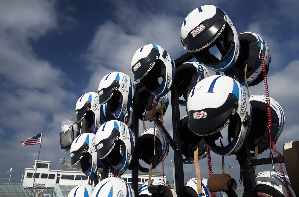 race car diver helmets on a rack at a race track