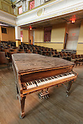 Empty concert hall or high school auditorium with decaying old grand piano and wooden seats, very bad condition.