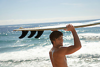 Man holding surfboard above head by ocean head and shoulders