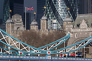 Weeks before the UK's Brexit from the European Union (31st January 2020), the British Union Jack flag flies over the Norman-era Tower of London and the northern steel suspension chains and hangers of Tower Bridge over which a tour bus passes, on 17th January 2020, in London, England.