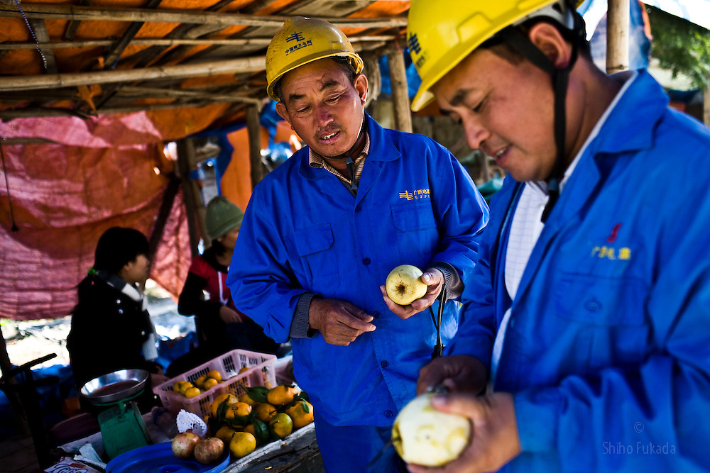 Chinese workers buy fruits from local shop near the Haiphong Thermal Power Plant construction site in Trung Son, Vietnam, Nov. 22, 2009. At the construction site here, a few miles northeast of the port city of Haiphong, an entire Chinese world has sprung up, including four walled dormitory compounds for the Chinese workers, restaurants with Chinese signs advertising dumplings and fried rice, and currency exchange shops.