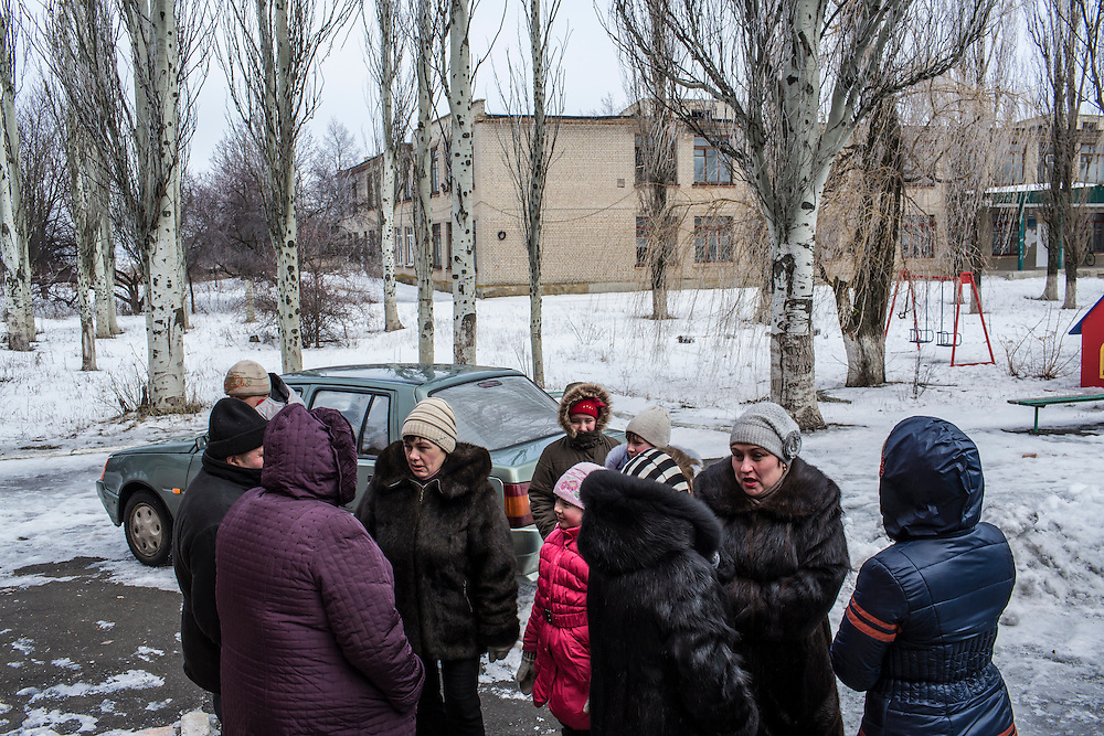MNOGOPOLYE, UKRAINE - JANUARY 24, 2015: Local residents gather in anticipation of a delivery of humanitarian aid by the International Committee of the Red Cross in Mnogopolye, Ukraine. ICRC aid deliveries are planned for the area approximately once per month, and supply food and hygiene items for more than one thousand people. CREDIT: Brendan Hoffman for The New York Times
