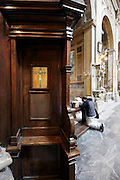 confessional and person on knees praying