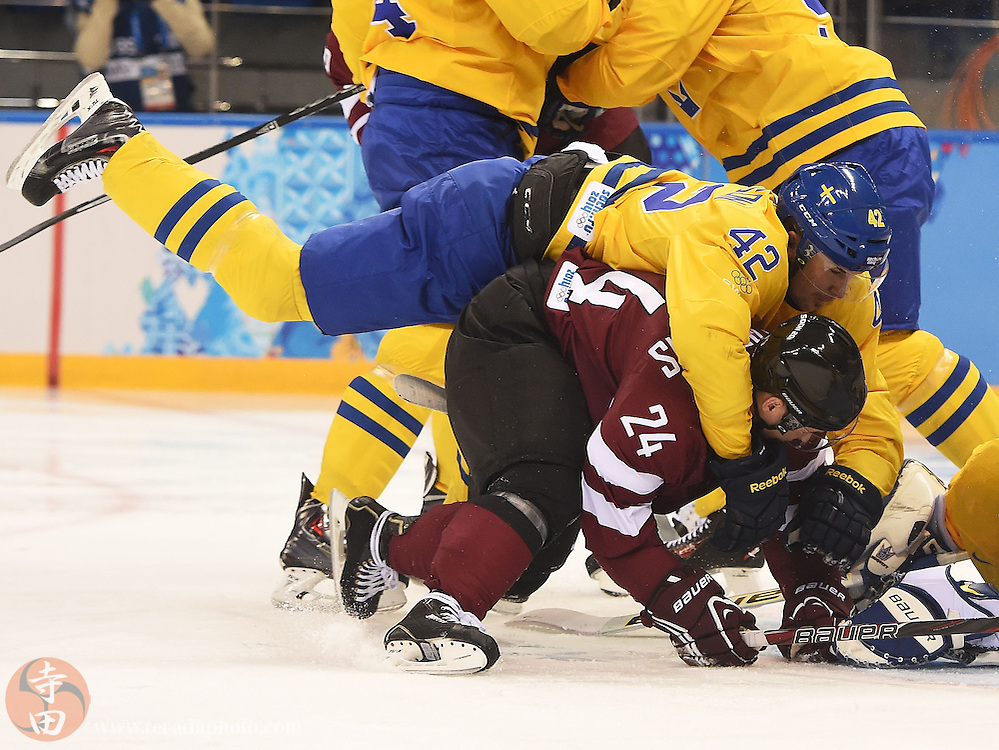 Feb 15, 2014; Sochi, RUSSIA; Sweden forward Jimmie Ericsson (42) falls on top of Latvia forward Mikelis Redlihs (24) in a men's preliminary round ice hockey game during the Sochi 2014 Olympic Winter Games at Shayba Arena.