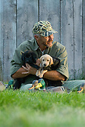 Yellow and black Labrador retriever puppies being held by a dog trainer.