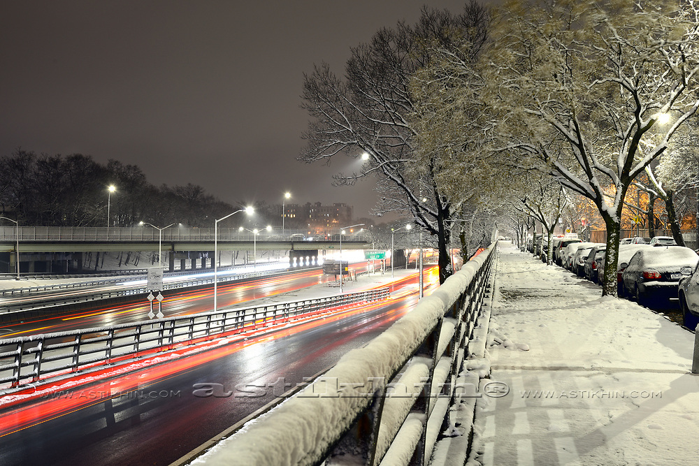 Car light at night on ice road in first snow in Brooklyn.
