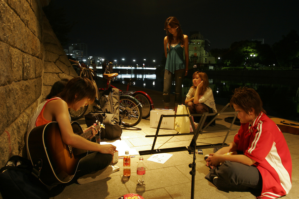 Hiroshima,  Young people  play  music under the Motoyasu Bashi (bridge) on the   Motoyasu-Gawa river in site of the  a bomb dome at the Peace Memorial Park A nightly gathering spot for many  young  People.