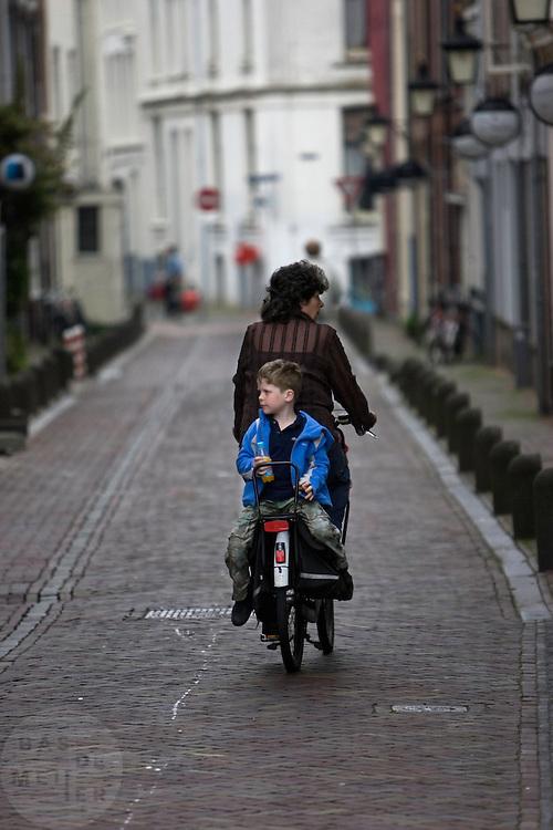 Een jongen zit achterop bij een vrouw op de fiets in de Korte Smeestraat in Utrecht.<br /> <br /> A boy is sitting backwards on a bike at the Korte Smeestraat in Utrecht.